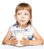 Cute little girl drinks milk using drinking straw. Isolated over white Stock Photos