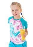 Cute little girl drinks orange juice Royalty Free Stock Photo