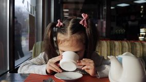 Cute little girl drinks tea with candy, sitting by the window and dreams stock video footage