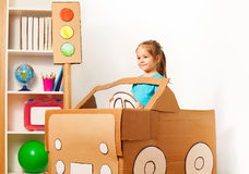 Cute little girl driving her toy cardboard car Stock Images