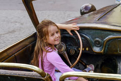 Cute little girl driving the sculpture car. Moscow Royalty Free Stock Photo