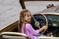Cute little girl driving the sculpture car. Moscow Royalty Free Stock Images