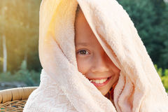 Cute little girl is drying off from swimming at summer day Stock Photos
