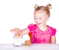 Cute little girl dunking cookie in milk Stock Photos