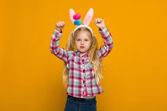 Cute little girl with Easter bunny ears holding colorful eggs royalty free stock image