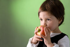 Cute little girl eating apple royalty free stock image