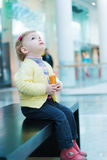 Cute little girl eating biscuit cake on bench Royalty Free Stock Images