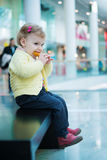 Cute little girl eating biscuit cake on bench Royalty Free Stock Photography