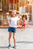 Cute little girl eating candy apple and posing at fair in amusement park. royalty free stock images