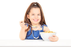 Cute little girl eating cereal from a bowl Stock Image