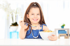 Cute little girl eating cereal from bowl seated on table Stock Image