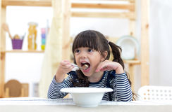 Cute little girl eating cereal with the milk. In the kitchen Royalty Free Stock Photo