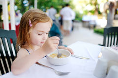 Cute little girl eating cereal Stock Images