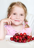 Cute little girl eating cherries Stock Images