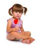 Cute little girl eating a colored lollipop Stock Photos