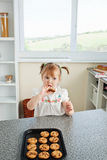 Cute little girl eating cookies secretly Royalty Free Stock Image