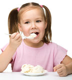 Cute little girl is eating cottage cheese Royalty Free Stock Photo