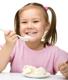 Cute little girl is eating cottage cheese Stock Photography