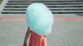 Little girl eating cotton candy in summer day. Cute little girl eating cotton candy and straightening her hair in a city park in sunny summer day. slow motion stock video