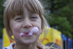 Cute little girl eating cotton candy. A walk in the summer park. Summer vacation. Outdoor Activities. Stock Photo