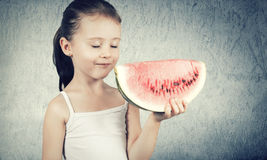 Cute little girl eating a delicious red watermelon Royalty Free Stock Photography