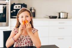 Cute little girl eating fresh carrot in white kitchen royalty free stock image