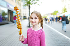 Cute little girl eating fried potato on a stick Royalty Free Stock Photo