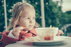 Cute little girl eating fries and tomato sauce royalty free stock images