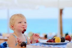Cute little girl eating fruits in resort restaurant Royalty Free Stock Images