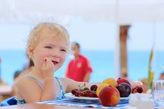 Cute little girl eating fruits in resort restaurant Royalty Free Stock Photo