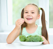Cute little girl is eating green grapes Stock Photo