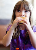 Cute little girl eating a hamburger. For lunch royalty free stock photo