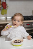 Cute little girl eating healthy porridge. With bilberry with plastic spoon, while sitting in the high chair at table in the kitchen. Image with selective focus Royalty Free Stock Photo
