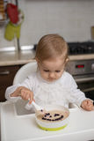 Cute little girl eating healthy porridge. With bilberry with plastic spoon, while sitting in the high chair at table in the kitchen. Image with selective focus Stock Photos