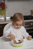 Cute little girl eating healthy porridge. With bilberry with plastic spoon, while sitting in the high chair at table in the kitchen. Image with selective focus Stock Photo
