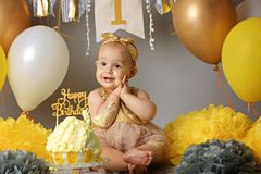 Cute little girl eating her first birthday cake