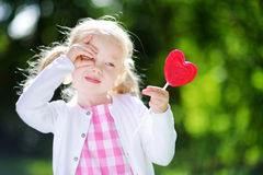 Cute little girl eating huge heart-shaped lollipop outdoors Stock Photos