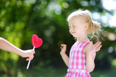 Cute little girl eating huge heart-shaped lollipop outdoors Royalty Free Stock Photo