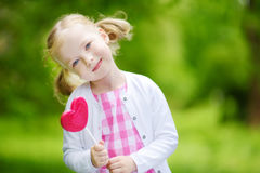 Cute little girl eating huge heart-shaped lollipop outdoors on beautiful summer day Stock Images