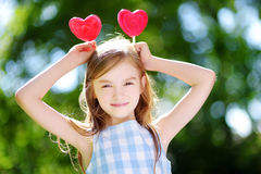 Cute little girl eating huge heart-shaped lollipops outdoors Stock Photography