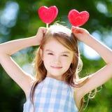 Cute little girl eating huge heart-shaped lollipops outdoors Stock Photo