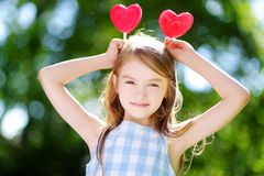 Cute little girl eating huge heart-shaped lollipops outdoors Stock Images