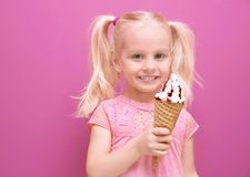 Cute little girl eating ice cream on color background royalty free stock images
