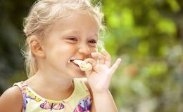 Cute little Girl Eating Ice-Cream on colorful background stock photo