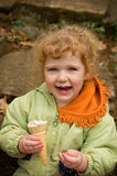 Cute little girl eating an ice cream cone. Adorable little girl outdoors eating an ice cream cone Royalty Free Stock Image