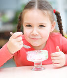 Little girl is eating ice-cream in parlor Stock Images
