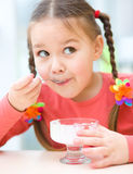 Little girl is eating ice-cream in parlor royalty free stock photography