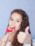 Cute little girl eating a lollipop Royalty Free Stock Photography