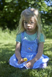 Cute little girl eating a lollipop on the grass in summertime Stock Images
