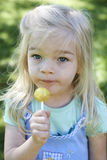 Cute little girl eating a lollipop on the grass in summertime Stock Photos